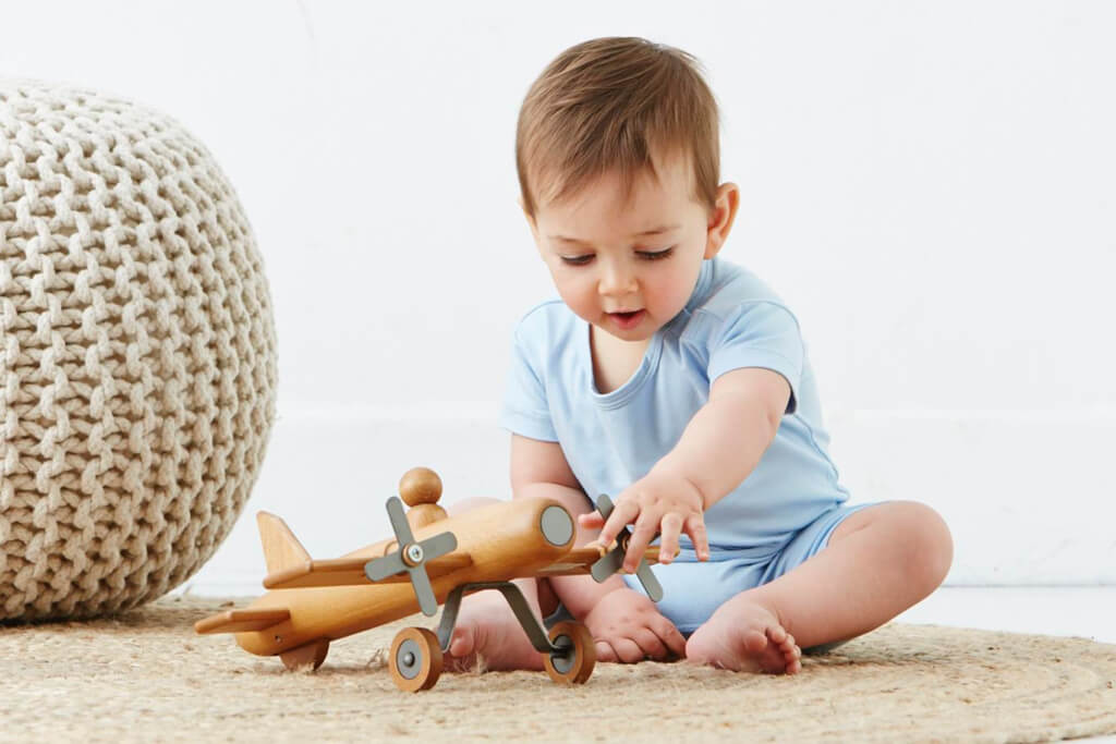 Bamboo baby shirt and shorts in light blue playing with toy plane