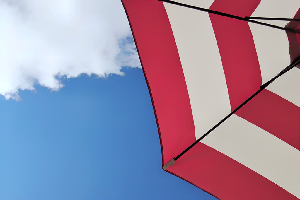 Red and white umbrella against a blue sky