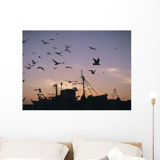 Sea Gulls Flying Over Fishing Boats At Dusk In The Harbor Wall Mural