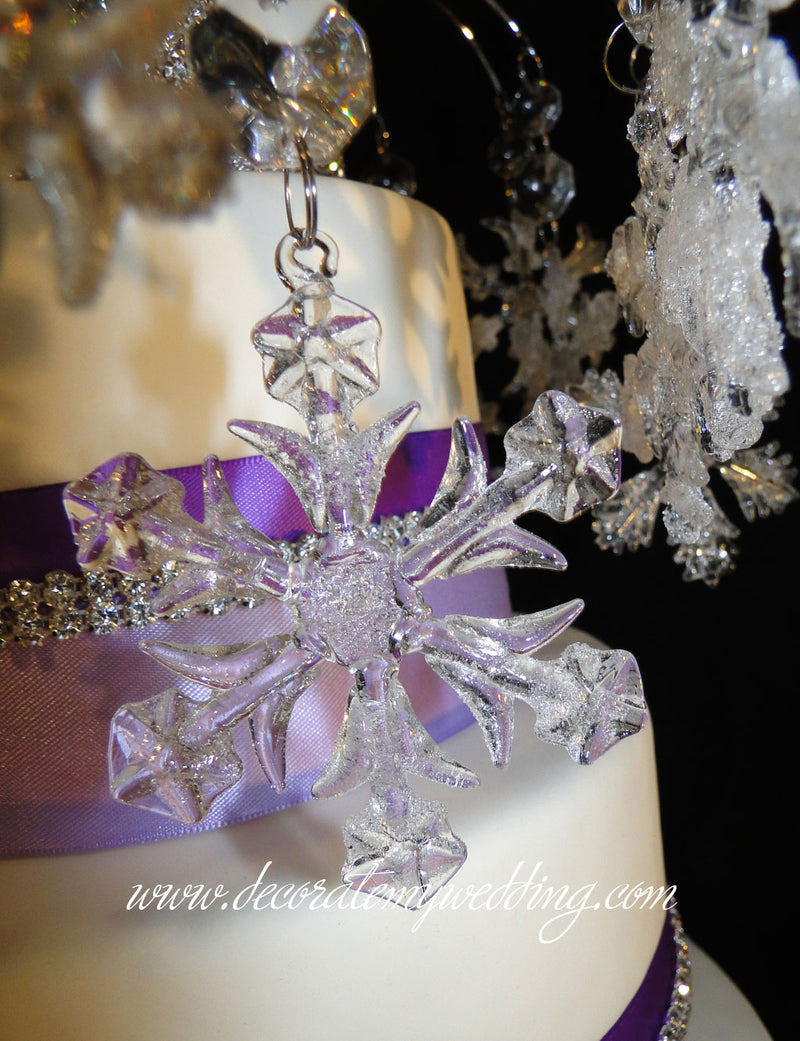 A close up look at the delicate snowflakes that dangle off the arch spokes of this winter wonderland cake topper.