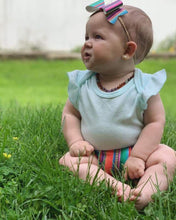 Baby Girl sitting in grass wearing Willow baltic amber teething and crystal necklace by MacRae Naturals