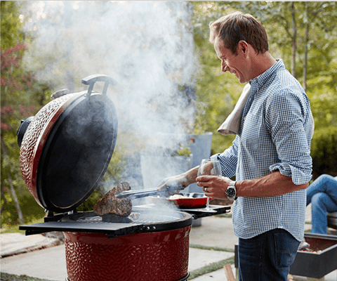 man turning over grilled steak on BBQ while drinking wine