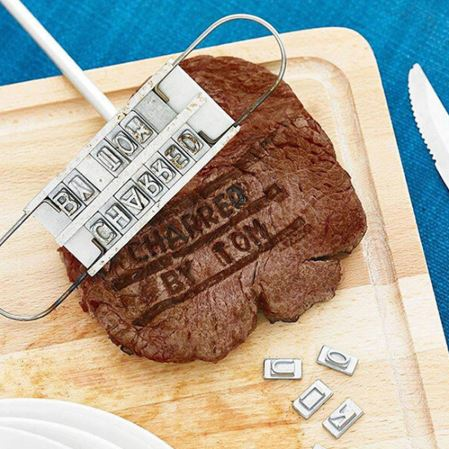 The grilling and cook out branding iron for steaks with letters and branded with charred by tom