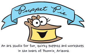 An Art Studio for for fun quirky puppets and workshops in the heart of Phoenix, Arizona. Photo is of a blue banner with the words Puppet Pie in the banner. It is magically floating over a piece of custard pie that has eyeballs and is smiling