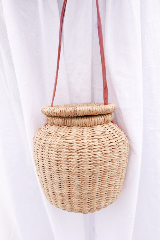 The natural Alobahe handbag is handwoven with straw called Kinkahe in Sherigu, Ghana. The shape is versatile and opens from the lid lifted vertical with an adjustable leather strap that can be worn as a crossbody or a handheld bag. This product supports a community with employment, educational opportunities for the children and improve the work environment.