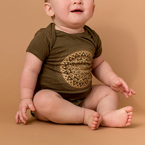 baby wearing olive colored onesie t-shirt with mandala printed in tan on front