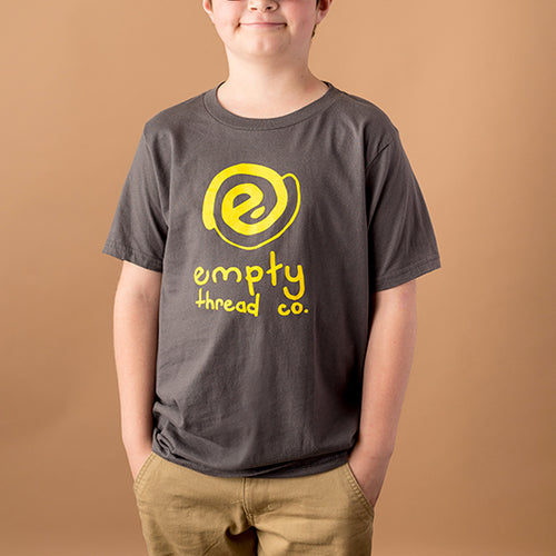 youth white male wearing a dark grey tee shirt with empty thread company logo in yellow with text below that says empty thread co