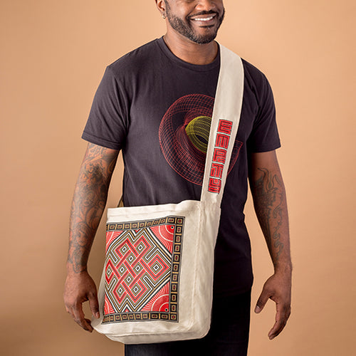 african american male wearing the colorado wire frame design and carrying a cavas market bag with buddhist symol of the endless knot screen printed on it