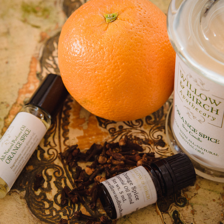 Orange Spice scented natural bath, beauty, and fragrance products by Willow & Birch Apothecary pictured with fresh orange and clove buds