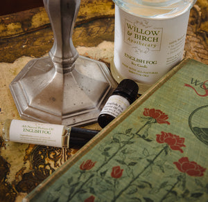 English Fog scented natural bath, beauty, and fragrance products by Willow & Birch Apothecary pictured with antique candlestick and antique book