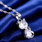 silver cat pendant necklace with clear berg crystals on blue cloth