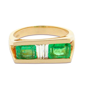 two emerald cut emeralds with baguette cut diamonds in between, set in a 14 k yellow gold ring