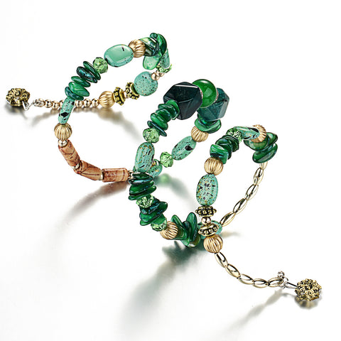 Picture of green version of bangles, beads and stone bracelet stretched out.