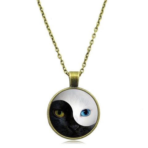 Yin and Yang blue-eyed cat necklace in bronze hanging down from chain.