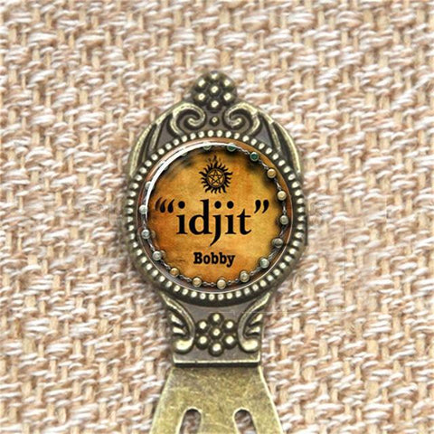 """idjit"" pendant bookmark in bronze against a fabric background."