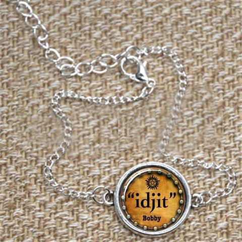 """idjit"" pendant bracelet in silver against a fabric background."