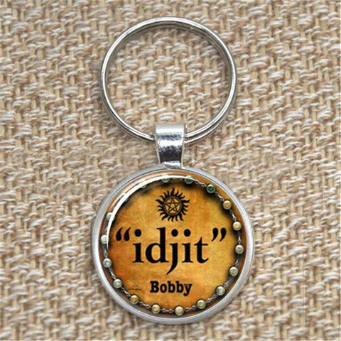 """idjit"" pendant key chain in silver against a fabric background."