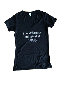 "Black vee neck tee with ""I am deliberate and afraid of nothing"" saying"