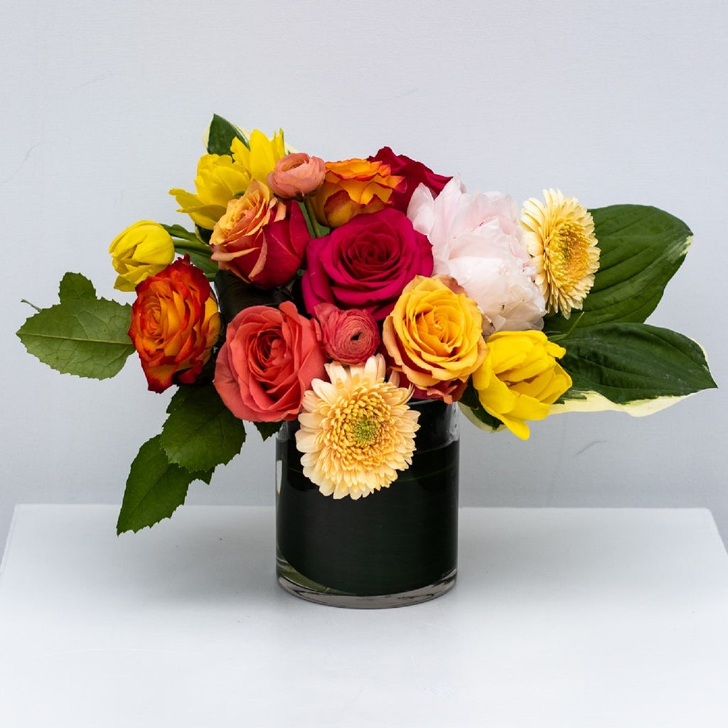 Mother's day flower arrangement of rose, yellow tulips, ranunculus, daisies and a peony.