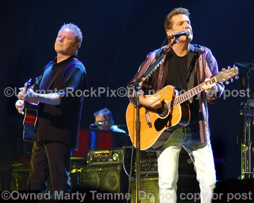 Photos of Glenn Frey and Don Henley of The Eagles playing acoustic guitar in concert by Marty Temme
