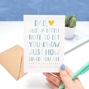 "A father's day card by Joanne Hawker being held in her right hand, with a green pen on a white and blue background. The card reads ""Dad, just a little note to let you know just how loved you are - happy fathers day"". The letters are in varying shades of blue with a yellow heart."