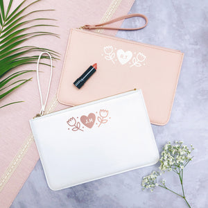 A white and pink personalised initial bridesmaid wristlet flat lay featuring the pouches lying on a grey background with lipstick, foliage and flowers used as props.