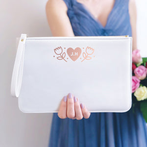 A white, personalised Bridesmaids wristlet held by Joanne Hawker in a lilac bridesmaid dress with a bunch of pink and red roses.