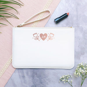 A white personalised initial bridesmaid wristlet flat lay featuring the pouches lying on a grey background with lipstick, foliage and flowers used as props.
