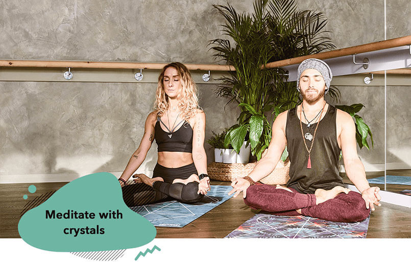couple-wearing-healing-crystal-necklaces-meditating-at-home