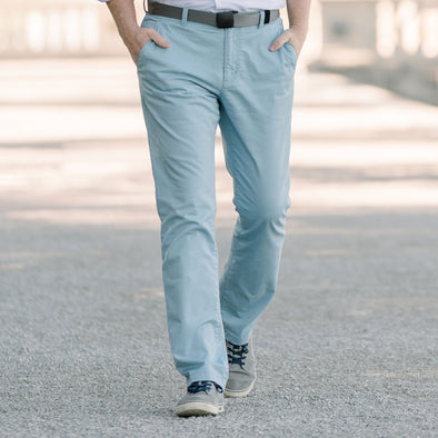 Man walking in a park wearing light blue flat front stretch pants