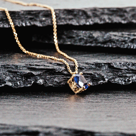 A pendent in yellow gold with an iolite cushion cut stone
