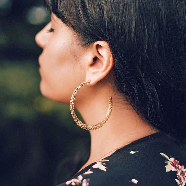 Gold hoop earrings being worn by a women.