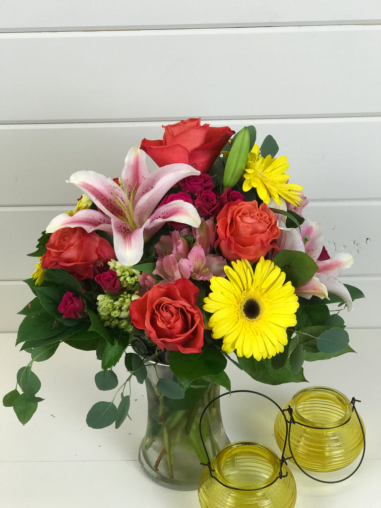 A floral arrangement of wildflowers that are bright and colorful with lilies, Gerber daisies,  and roses local flower shop in Belmar, New Jersey Gig Morris Florist