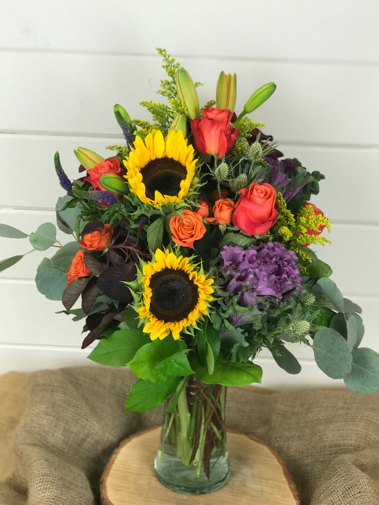 Fall collection of purples, oranges, yellows and reds. Includes Lilies, sunflowers, roses, spray roses, purple kale in a tall vase