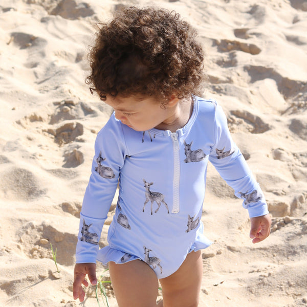 Little girl at beach wearing Willow Swim Sophia girls swimsuit in Dreamy Fawn