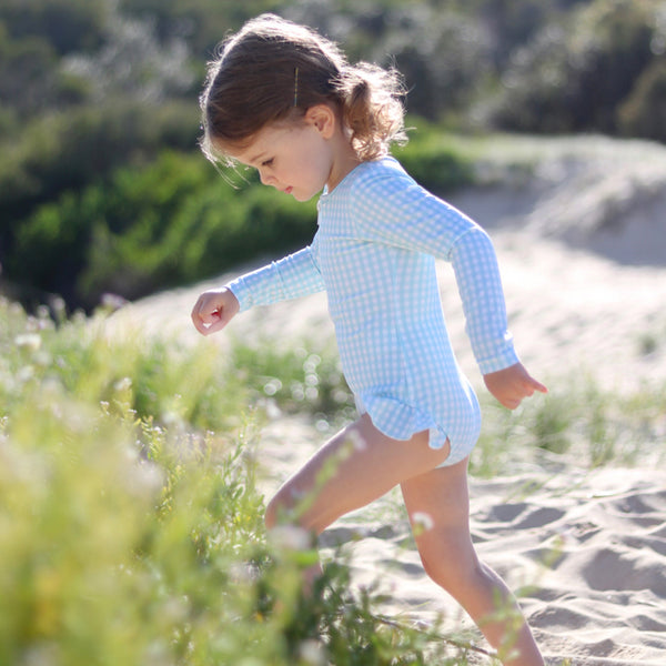 Little girl at beach wearing Willow Swim Sophia girls swimsuit in Minty Gingham