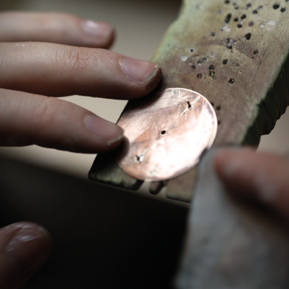 Sanding of a copper dial blank in preparation for application of powdered enamel
