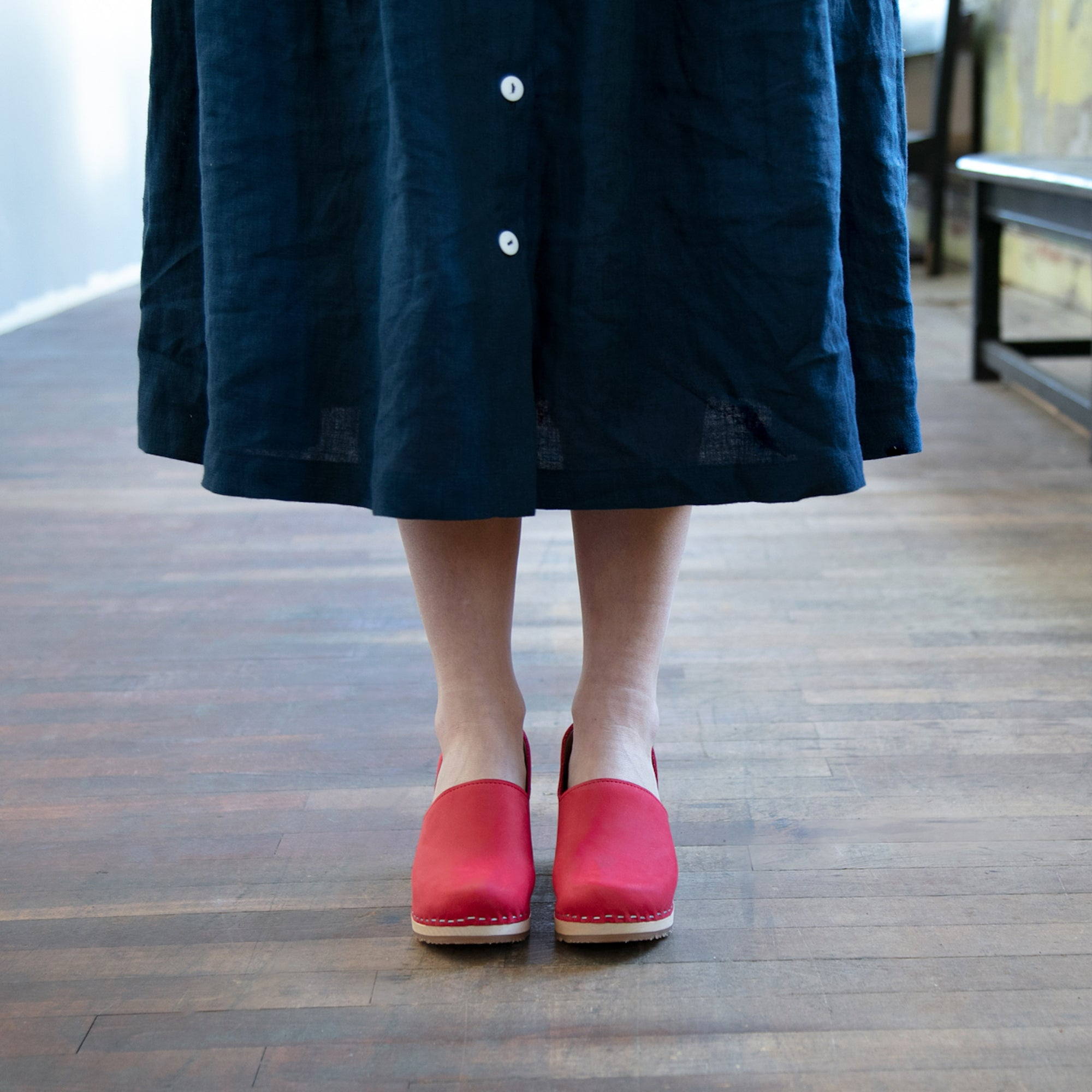 Woman in dress wearing red clogs