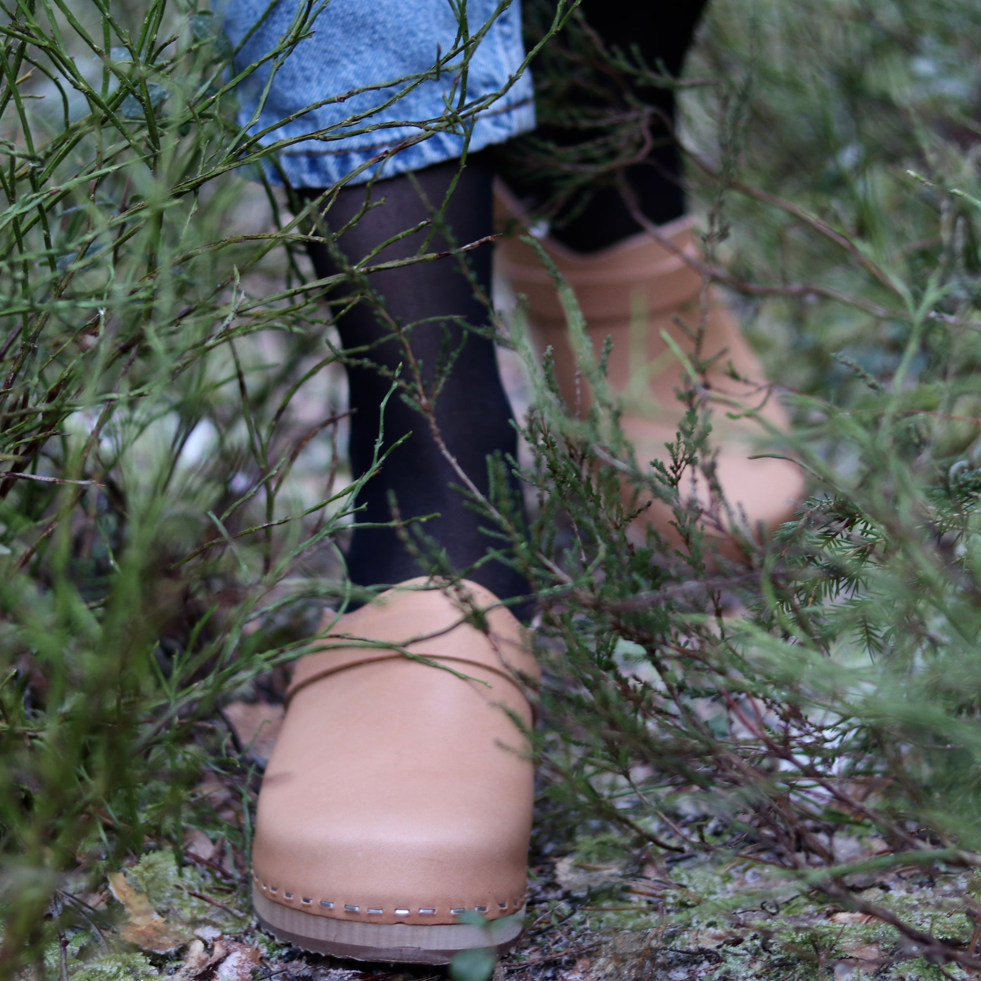 A person walking through the long grass with tan clogs
