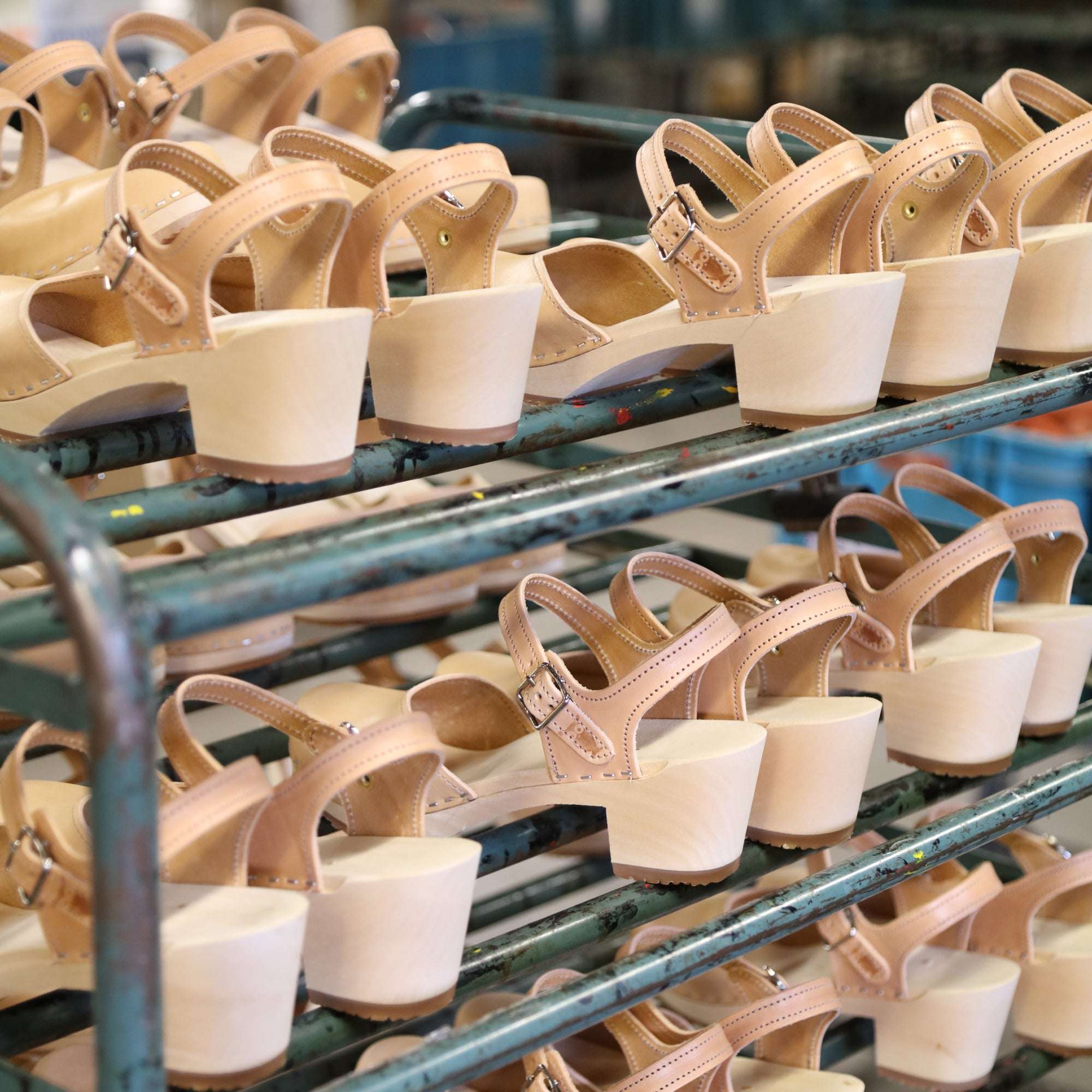 Multiple pairs of nude sandals on a production rack