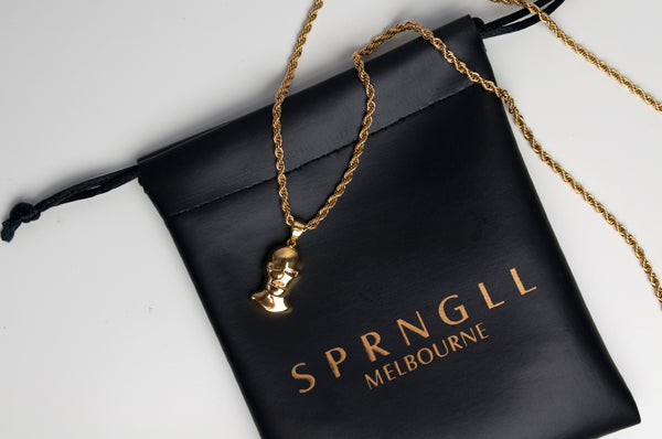 Gold Balaclava Pendant Chain on top of SPRNGLL branded gift bag