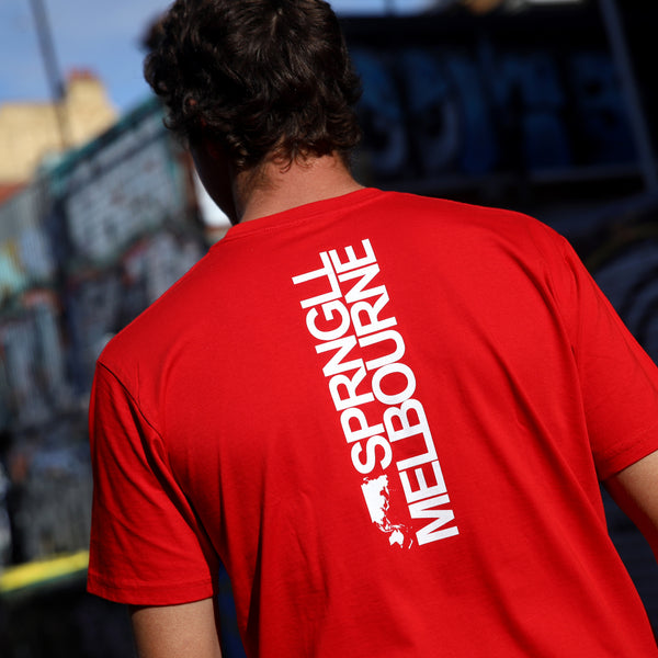 A man wearing a red tee with bold writing on it. Facing the other way