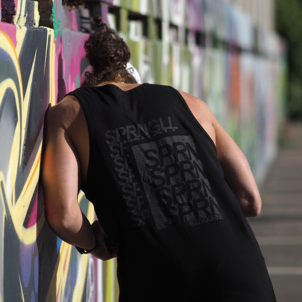 Man wearing a black singlet with SPRNGLL printed on the back looking away and down