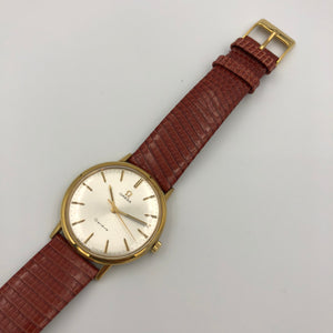 Gold watch with white face and red strap