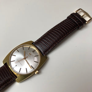 Tissot watch with white face, gold case and brown leather strap.