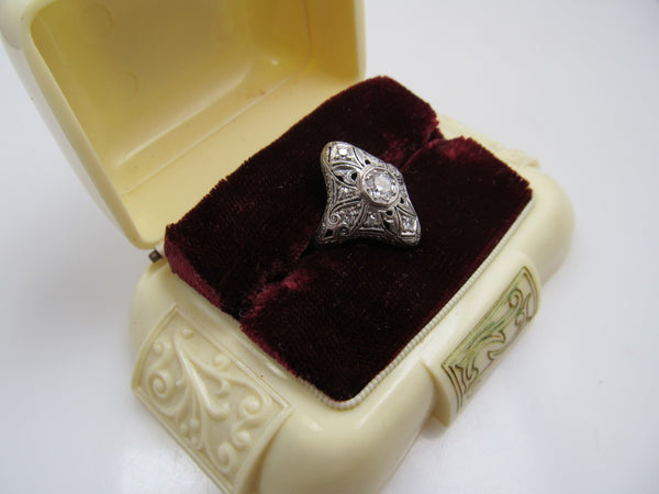 19k white gold filigree ring with a .25ct center OEC diamond.   Circa 1920.