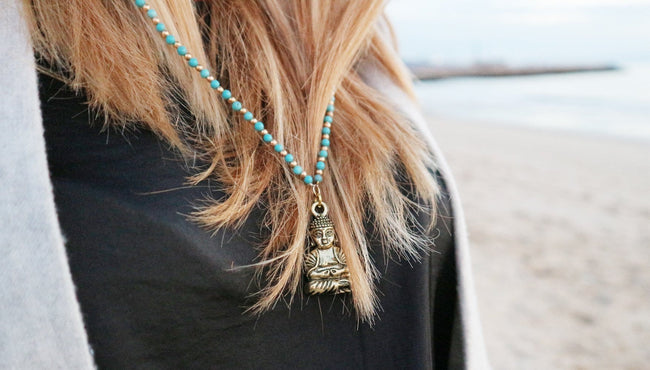 Girl is wearing Unisex Long Yoga Inspired Turquoise Happy Buddha Necklace on the beach
