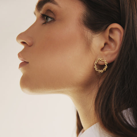 Woman wearing gold circle stud earrings