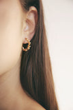 Woman wearing small gold swirl hoop earrings