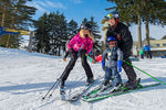 A family of skiers gets ready to head down the hill